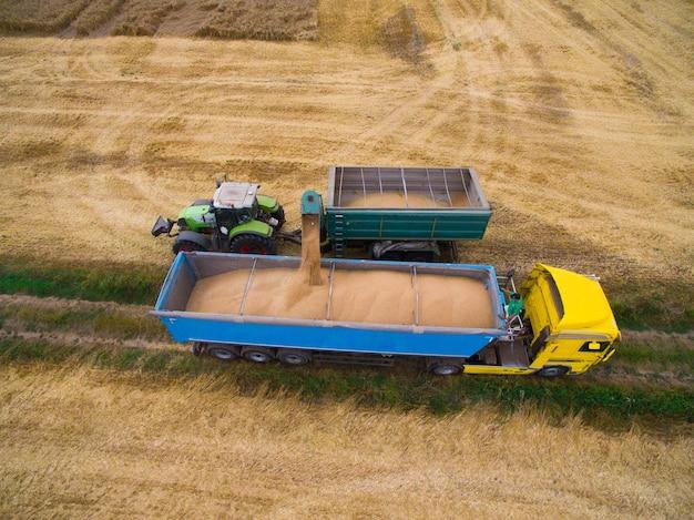 Luchtfoto van vrachtwagen die tarwe uit het veld oppikt