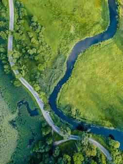 Luchtfoto van weg die door rivier onder bomen gaat