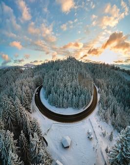 Luchtfoto van winterlandschap met besneeuwde bergheuvels en kronkelende bosweg in de ochtend.