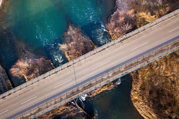 Luchtfoto van witte brug over blauwe water en steenachtige eilanden.