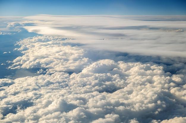 Luchtfoto van witte gezwollen wolken gezien vanuit een vliegtuig.