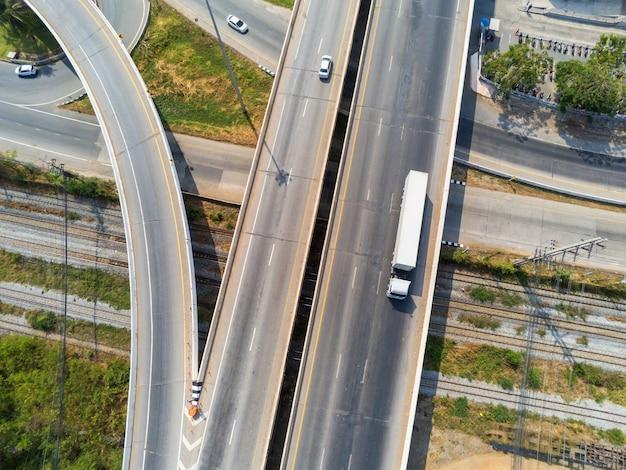 Luchtfoto van witte vrachtvrachtwagen op snelweg weg met container, transport concept., import, export logistieke industriële vervoer over land op de snelweg asfalt