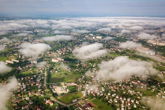 Luchtfoto van witte wolken boven een stad of dorp met rijen gebouwen en bochtige straten tussen groene velden in de zomer. platteland landschap van bovenaf.