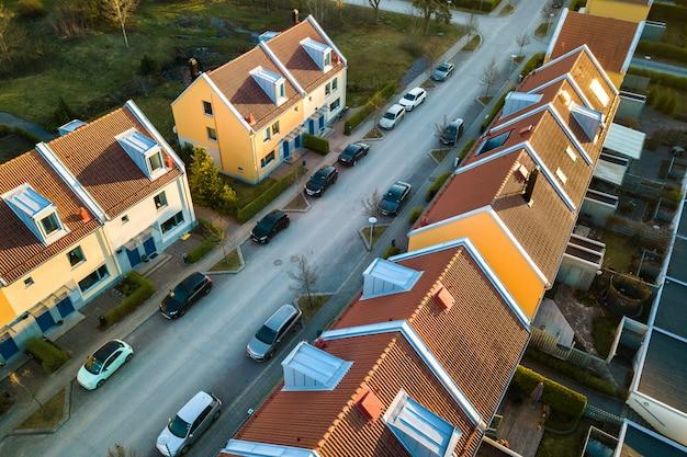 Luchtfoto van woonhuizen met rode daken en straten met geparkeerde auto's in landelijke stad. rustige buitenwijken van een moderne europese stad.