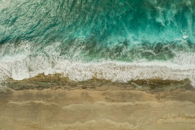 Luchtfoto van zand ontmoeten van het zeewater en de golven