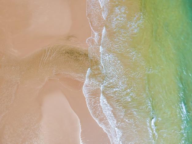 Luchtfoto van zandstrand en oceaan met golven
