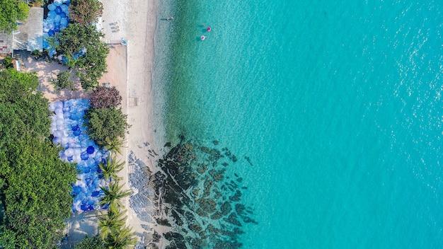 Luchtfoto van zandstrand met toeristen zwemmen.