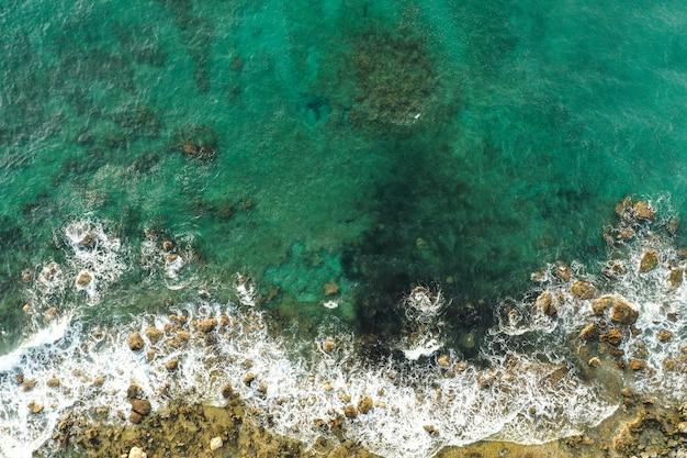 Luchtfoto van zee die rotsachtige kust ontmoet