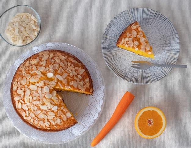 Luchtfoto van zelfgemaakte worteltaart met amandelen en sinaasappel. schotel met een stukje taart klaar om te eten