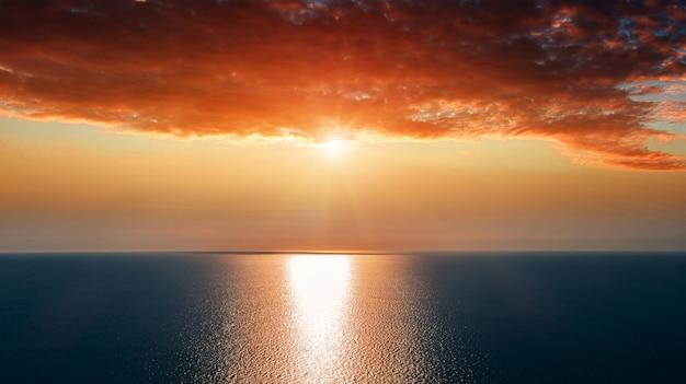 Luchtfoto van zon stijgt boven zee.