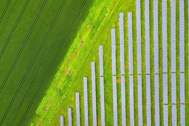 Luchtfoto van zonne-energiecentrale op groen veld. elektrische panelen voor het produceren van schone ecologische energie.