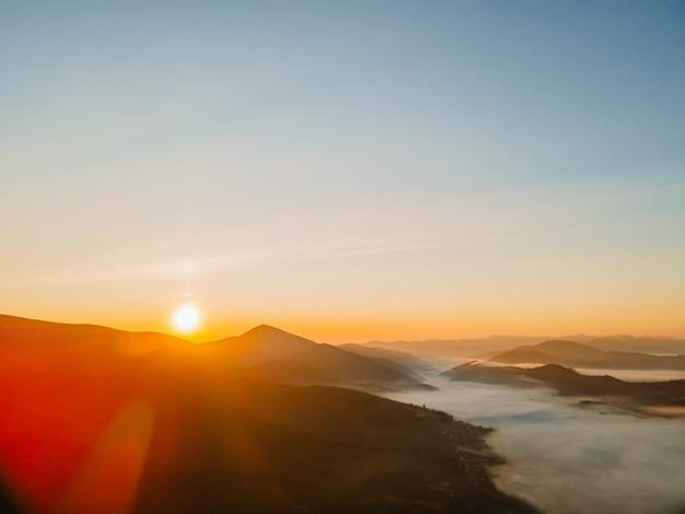 Luchtfoto van zonsopgang boven de kopieerruimte van de bergketen