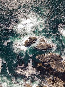 Luchtfoto verticaal van een zee met rotsachtige stenen