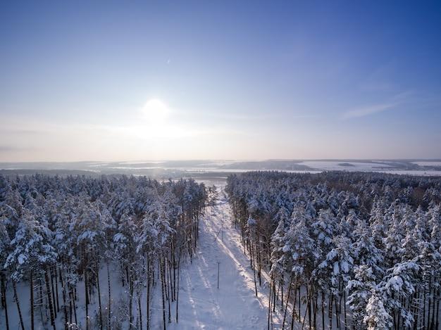 Luchtfoto winterbos zonnige dag in sneeuwval lake rivier landweg met kruising in bos