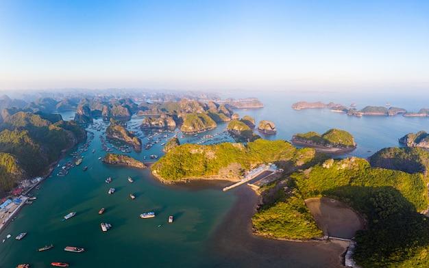 Luchtfoto zonsondergang van lan ha baai en cat ba eiland, vietnam, unieke kalkstenen rots eilanden en karst formatie pieken in de zee, drijvende vissersdorpjes en viskwekerijen van bovenaf. heldere blauwe lucht.