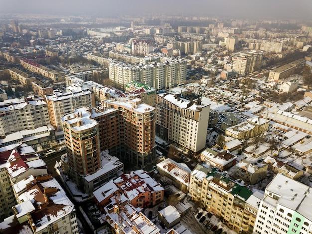 Luchtfoto zwart-wit winter bovenaanzicht van moderne centrum met hoge gebouwen en geparkeerde auto's op besneeuwde straten.