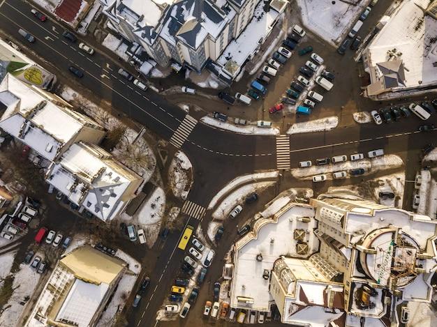 Luchtfoto zwart-wit winter bovenaanzicht van moderne stad met hoge gebouwen, geparkeerde en rijdende auto's langs straten met wegmarkering. stedelijke stadsgezicht, weergave van bovenaf.
