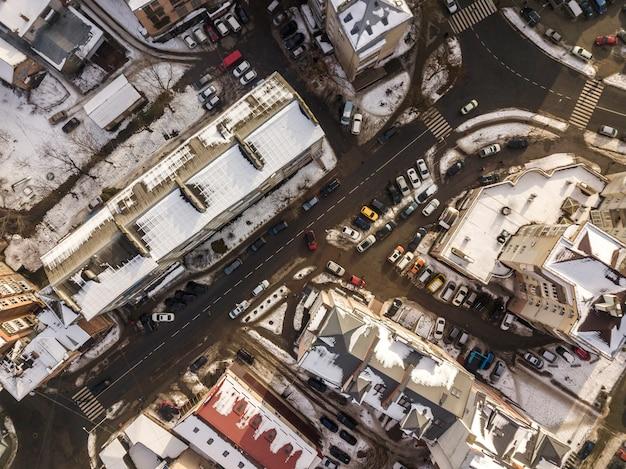 Luchtfoto zwart-wit winter bovenaanzicht van moderne stad met hoge gebouwen, geparkeerde en rijdende auto's langs straten met wegmarkering.