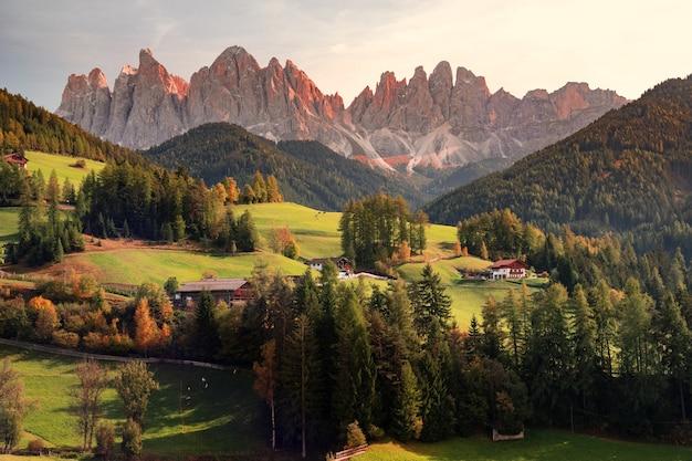 Luchtfotografie van huizen op groen veld bekijken berg onder witte en grijze hemel overdag