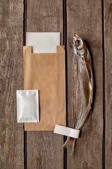 Luchtgedroogde sabelvis met kraftpapier zak nat doekje en papieren servet op houten oppervlak