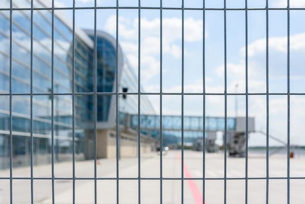 Luchthaven hek traliewerk op de achtergrond van passagiersbruggen voor passagiers aan boord.