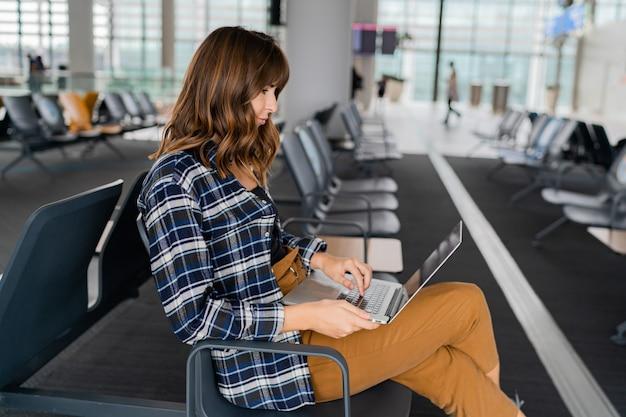 Luchthaven jonge vrouwelijke passagier met laptop zit in terminal hal tijdens het wachten op haar vlucht