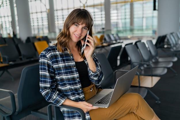 Luchthaven jonge vrouwelijke passagier met slimme telefoon en laptop zittend in terminal hal tijdens het wachten op haar vlucht