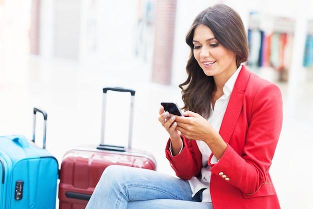 Luchthaven zakenvrouw op slimme telefoon bij gate wachten in terminal.