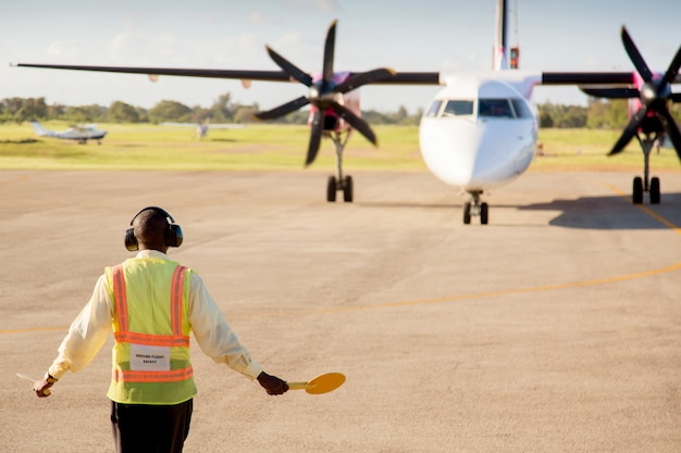 Luchthavenarbeider die een vliegtuig op de luchthavenbaan signaleert en leidt