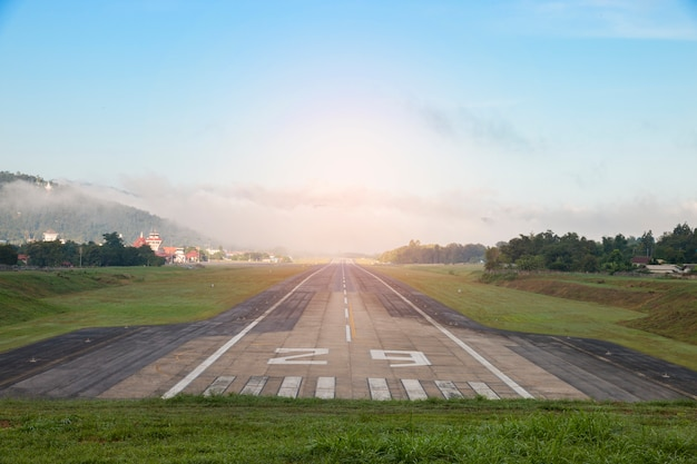 Luchthavenbaan met berg in platteland