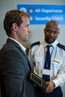 Luchthavenbeveiliger die een draagbare metaaldetector gebruikt om een forens te controleren