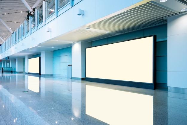 Luchthavenpassagiers en leeg reclamebord
