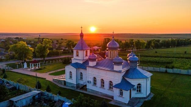 Luchthommelmening van een kerk bij zonsondergang. dorp in moldavië