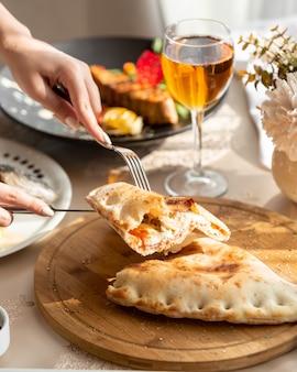 Luchtig brood gevuld met roomkaas en vlees op een houten bord
