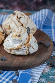 Luchtige meringue muffins met zwarte droge druiven op tafel.