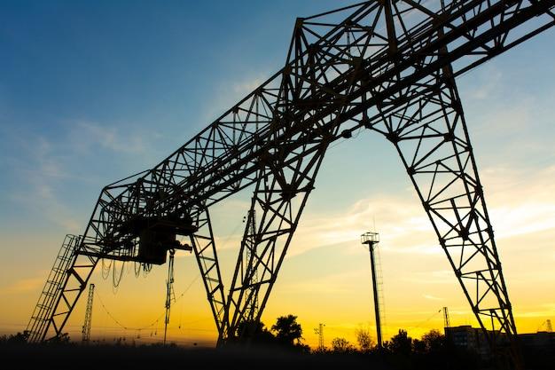 Luchtkraan bij het station. kraansilhouet op zonsondergangachtergrond. zware industrie concept.