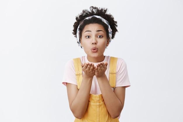 Luchtkussen verzenden. leuke en tedere jonge vrouw met donkere huid in trendy hoofdband over haar en gele overall, lippen vouwen en handpalmen vasthouden in de buurt van mond, mwah geven