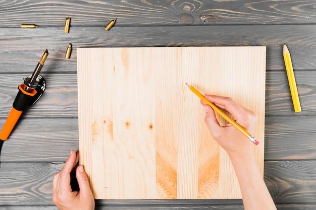 Luchtmening die van hand op houten raad over lijst trekken