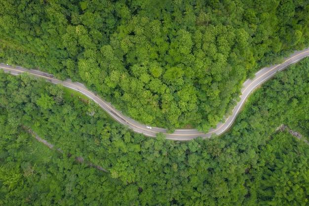 Luchtmening over bergweg die door tropisch regenwoudlandschap gaan in thailand.