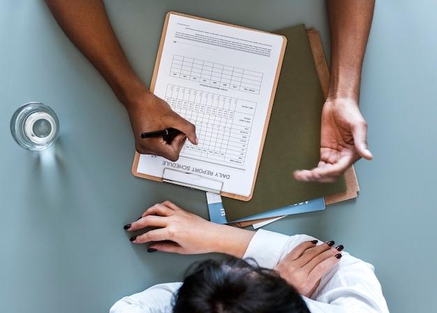 Luchtmening van arts die geduldige dagelijkse rapportcontrolelijst schrijven