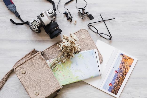 Luchtmening van camera, handtas, en kaart op houten bureau