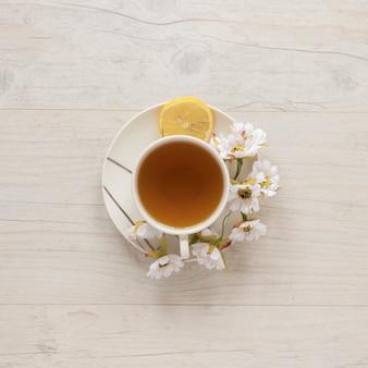 Luchtmening van citroenthee in kop met bloemen en citroen op schotel