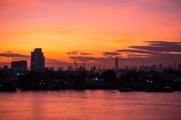 Luchtmening van de horizon van bangkok langs chaophraya-de schemering van de rivierzonsondergang