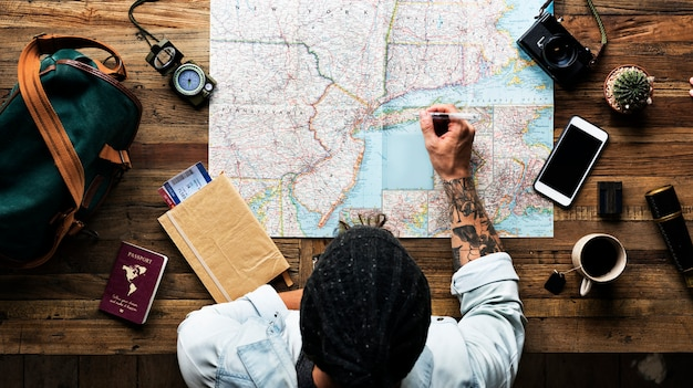 Luchtmening van de mens die de reis met kaart plannen