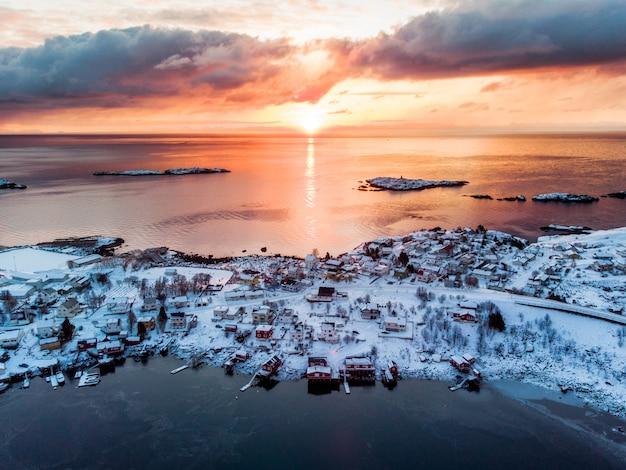 Luchtmening van de visserij van dorp op kust in de winter bij zonsopgangochtend