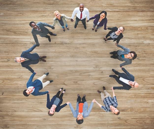 Luchtmening van diverse bedrijfsmensen die handen togeher groepswerk houden