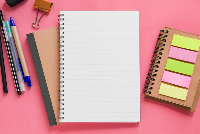 Luchtmening van diverse kantoorbehoeften op roze achtergrond