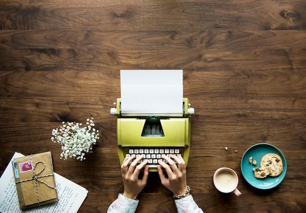 Luchtmening van een vrouw die op een retro schrijfmachineblanco document typen
