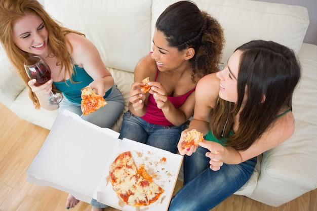 Luchtmening van gelukkige vrienden die pizza met wijn op bank eten