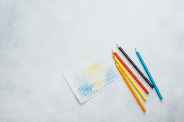 Luchtmening van getrokken document en kleurenpotloden op witte achtergrond